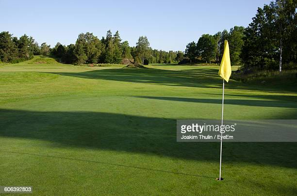 Yellow Flag In Hole On Golf Course Against Sky