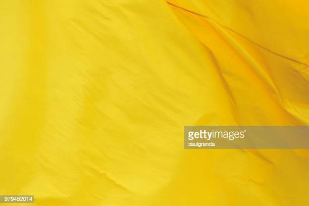 yellow flag waving close-up - textile stock photos and pictures