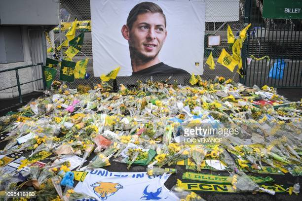 Yellow flowers are displayed in front of the portrait of Argentinian forward Emiliano Sala at the Beaujoire stadium in Nantes, on February 8, 2019. -...