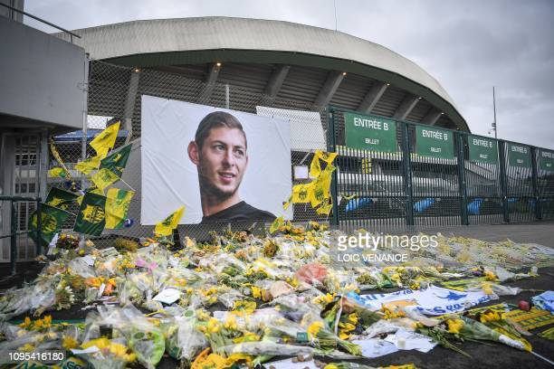Yellow flowers are displayed in front of the portrait of Argentinian forward Emiliano Sala at the Beaujoire stadium in Nantes on February 8 2019 FC...