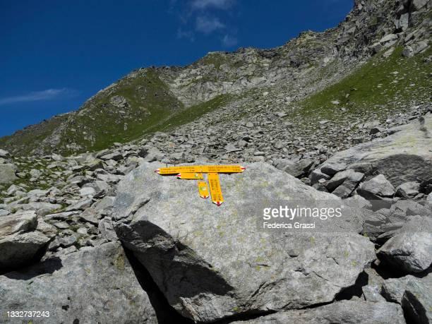 yellow footpath signs at passo di lucendro near gotthard pass - トレイル表示 ストックフォトと画像