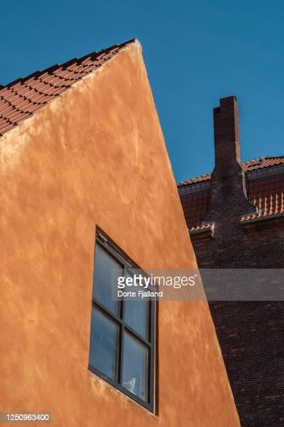 yellow gable end of old building with a window against a blue sky - dorte fjalland fotografías e imágenes de stock