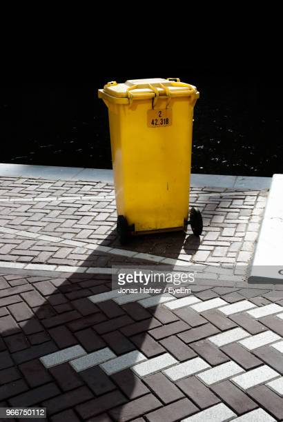 yellow garbage can on footpath during sunny day - jetée photos et images de collection