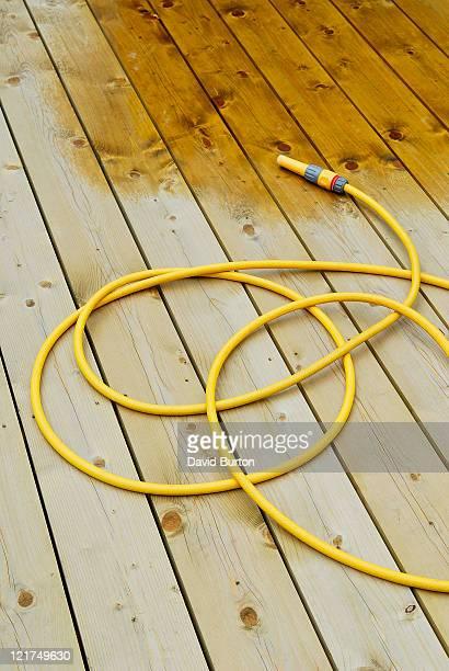 Yellow garden hose on timber decking