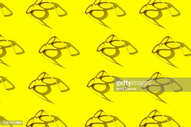 yellow glasses with shadow in sunlight. trendy colors of the year - サングラス ストックフォトと画像