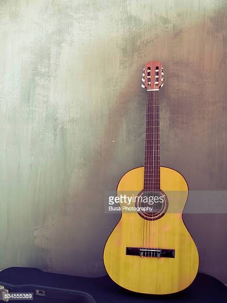 yellow guitar standing against a concrete wall - classical guitar stock photos and pictures