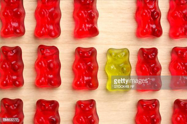 A yellow gummy bear between red gummy bears