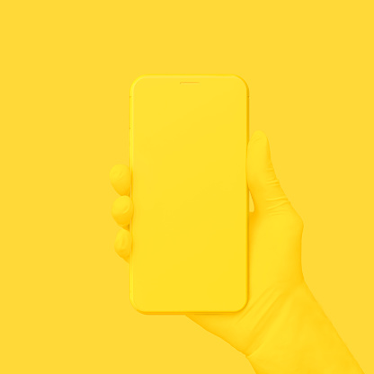 Yellow hand holding phone on yellow background. 1150630263