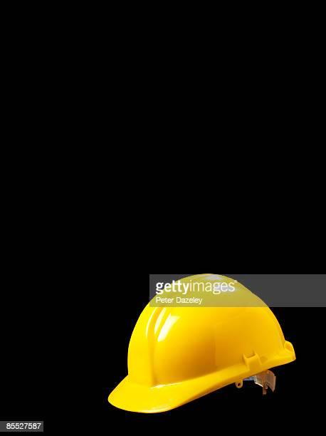 Yellow hard hat on black background.