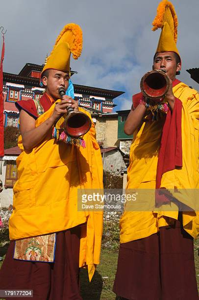 Yellow hat monks blowing horns at the Mani Rimdu Festival at Tengboche Monastery in the Everest Region of Nepal