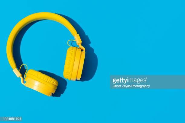 yellow headphones on a blue background - música pop fotografías e imágenes de stock