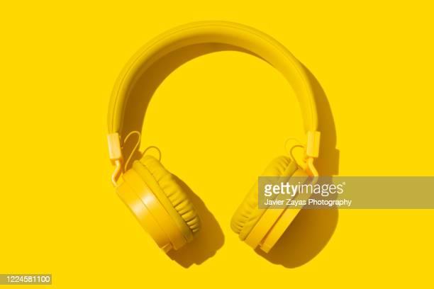 yellow headphones on a yellow background - ipod ストックフォトと画像