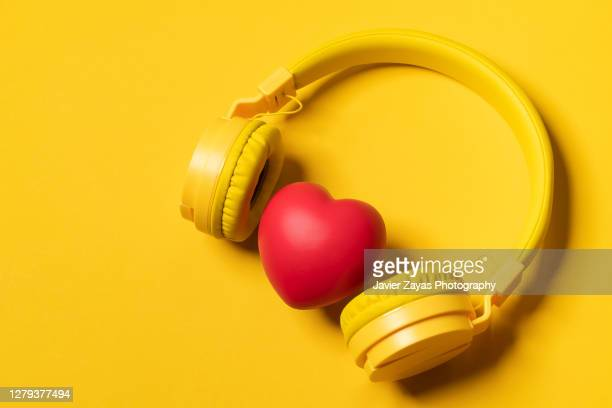 yellow headphones on yellow background and a heart - mp3 player stock pictures, royalty-free photos & images