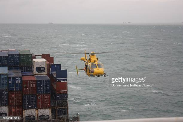 yellow helicopter flying towards container ship on sea - helicopter photos stock pictures, royalty-free photos & images