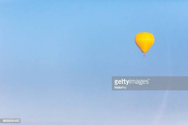 yellow hot air ballon against clear blue sky. chiemsee, chiemgau, bavaria, germany - leichter stock-fotos und bilder