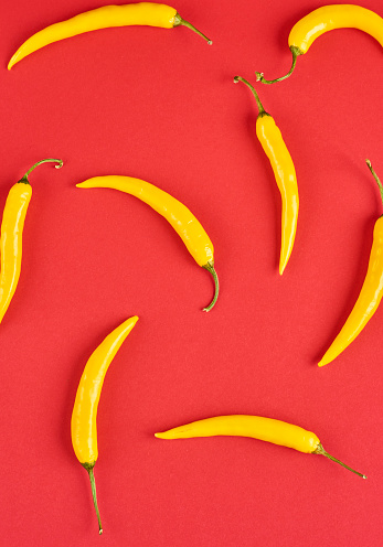 yellow hot chili peppers, popular spices concept - decorative pattern of red hot chili with green tails on red background, beautiful red collage of freely lying peppers, top view, flat lay 862048740