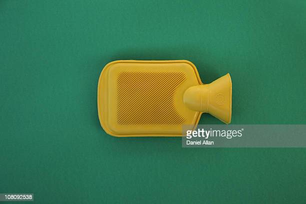 Yellow hot water bottle against green back ground