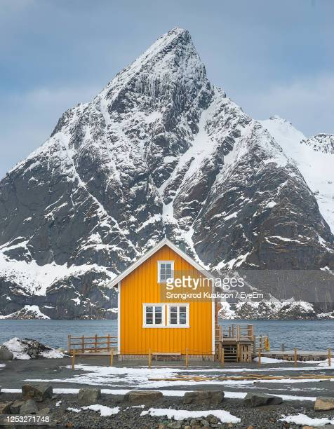 yellow house against snowcapped mountain - norway stock pictures, royalty-free photos & images
