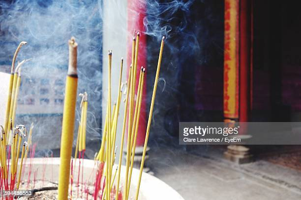 Yellow Incenses Burning In Pot In Temple