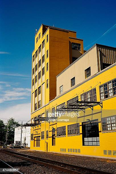 CONTENT] Yellow industrial building against blue sky rail tracks in foreground Canon Canonet GIII Lens Canon 40mm f/17 Film Kodak Ektar 100