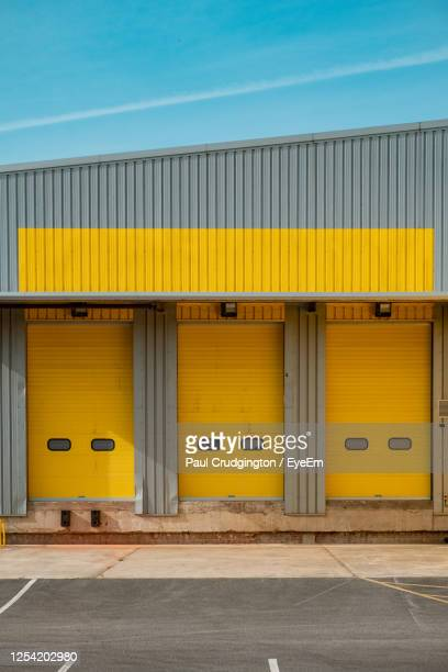 yellow industrial buildings against blue sky - building exterior stock pictures, royalty-free photos & images