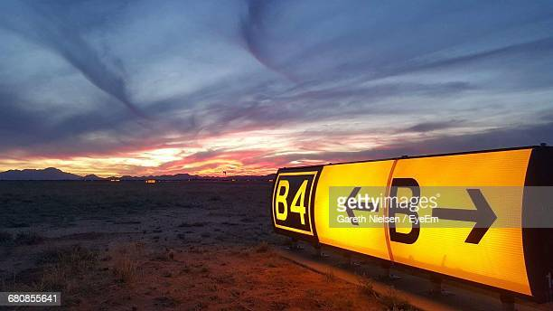Yellow Information Sign On Field Against Cloudy Sky During Sunset