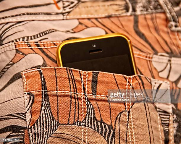 Yellow IPhone 5C in back pocket of stamped trousers
