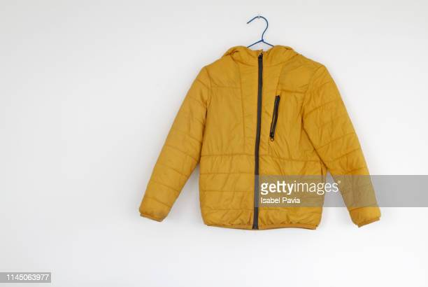 yellow jacket hanging on wall - coat stockfoto's en -beelden