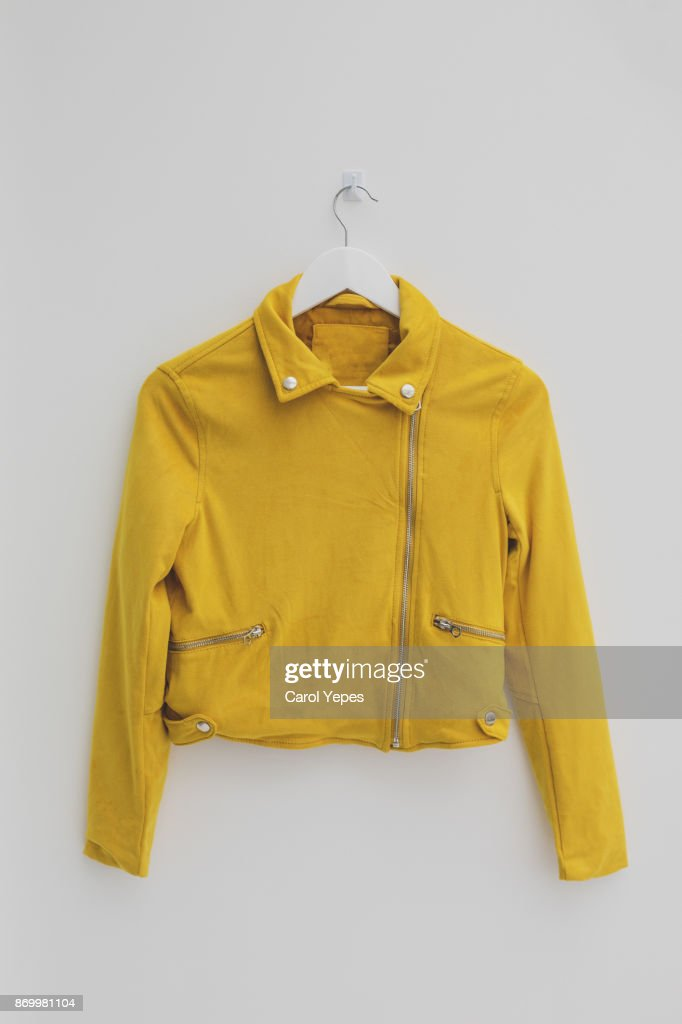 yellow jacket hung on rack in diy fashion studio workshop space : Stock Photo