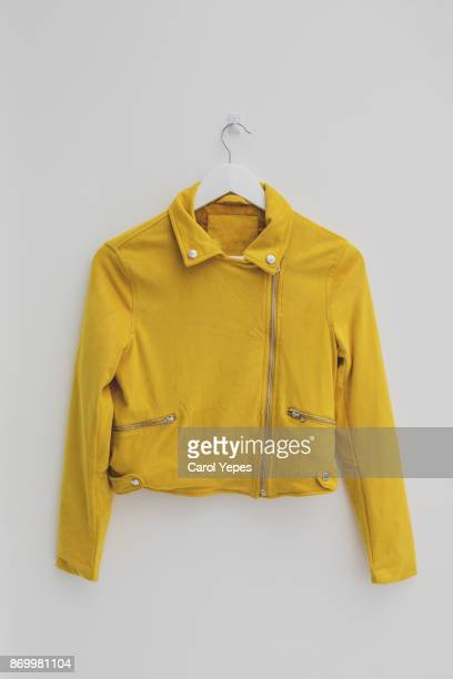 yellow jacket hung on rack in diy fashion studio workshop space - top garment stock photos and pictures