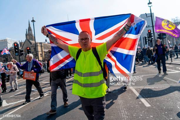 A yellow jacket protester holds up a Union flag as ProBrexit demonstrators gather in Parliament Square in central London on March 29 2019 British MPs...