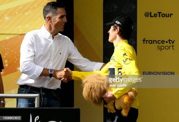 Yellow jersey Geraint Thomas of Great Britain and Team Sky is congratulated by former Tour de France winner Miguel Indurain following stage 20 of Le...