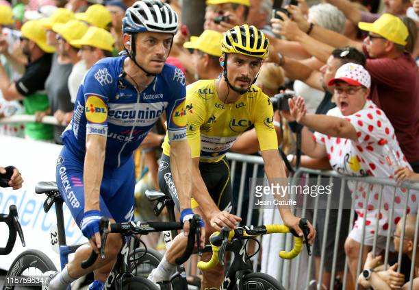 Yellow jersey Julian Alaphilippe of France and Deceuninck-Quick Step crosses the finish line with teammate Dries Devenyns of Belgium and...