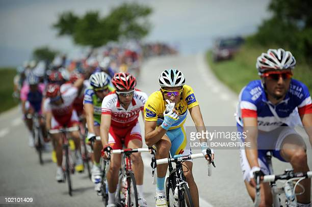 Yellow jersey of overall leader Alberto Contador eats as he rides in the pack on June 7 in the 191 km second stage run between EvianlesBains and...