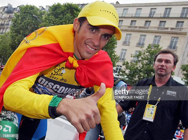 Yellow jersey Spain's Alberto Contador gives a thumbs up as his team manager Johan Bruyneel looks on after he celebrated his victory at the enf of...