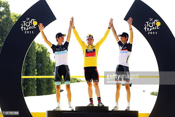 Yellow Jersey winner Cadel Evans of team BMC celebrates with Andy Schleck and Frank Schleck of team Leopard Trek on the podium after the twenty first...