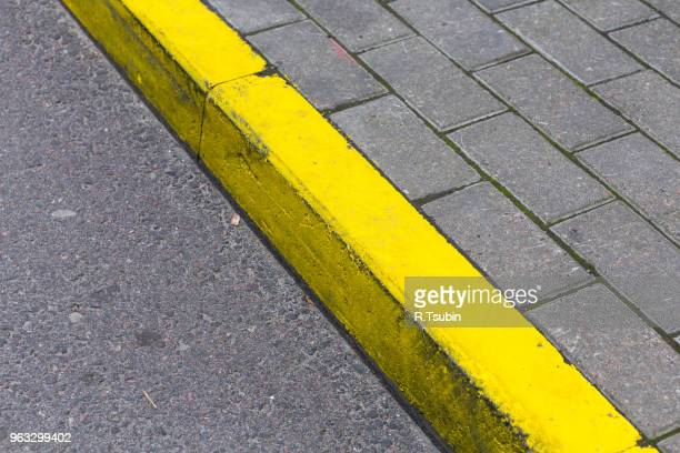 yellow kerb line on the asphalt road - curb stock pictures, royalty-free photos & images