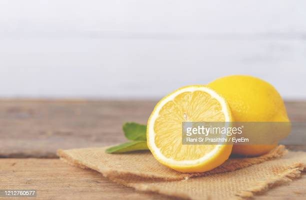 yellow lemon and half place on the brown sack and wooden table - レモン ストックフォトと画像