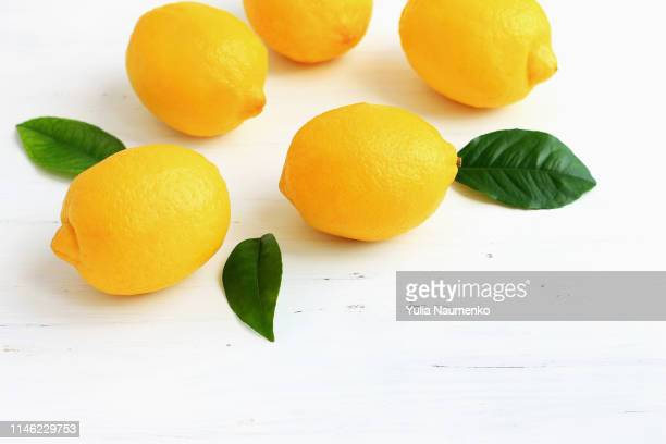 yellow lemons on white wooden background - レモン ストックフォトと画像