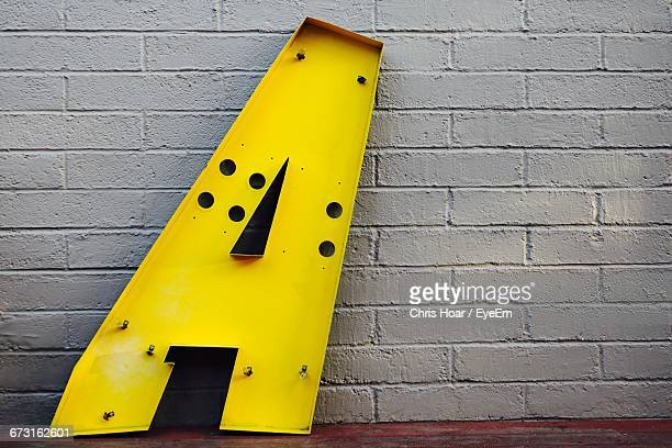 Yellow Letter A Against Brick Wall