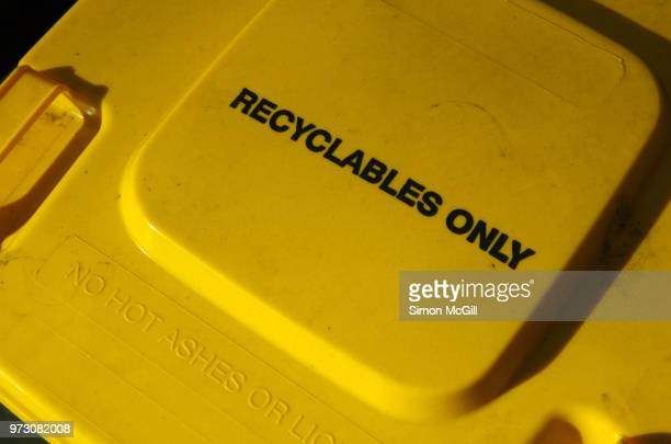 yellow lid of a plastic domestic recycling bin with 'recyclables only' and 'no hot ashes or liquids' written on it - rubbish bin stock pictures, royalty-free photos & images