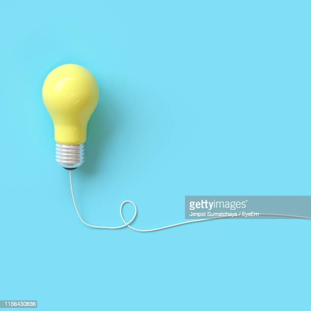yellow light bulb against blue background - single object stock pictures, royalty-free photos & images