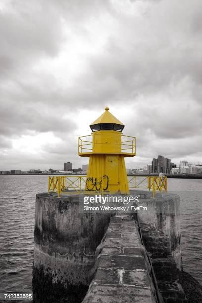 Yellow Lighthouse By Sea Against Sky