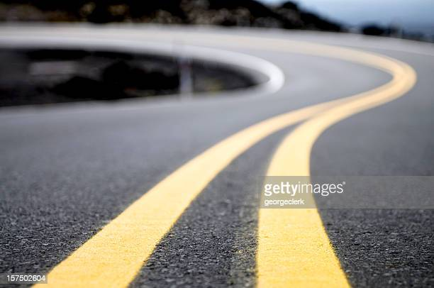yellow lines on a winding road - weg stockfoto's en -beelden