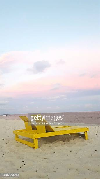 Yellow Lounge Chairs On Sea Shore Against Sky During Sunset