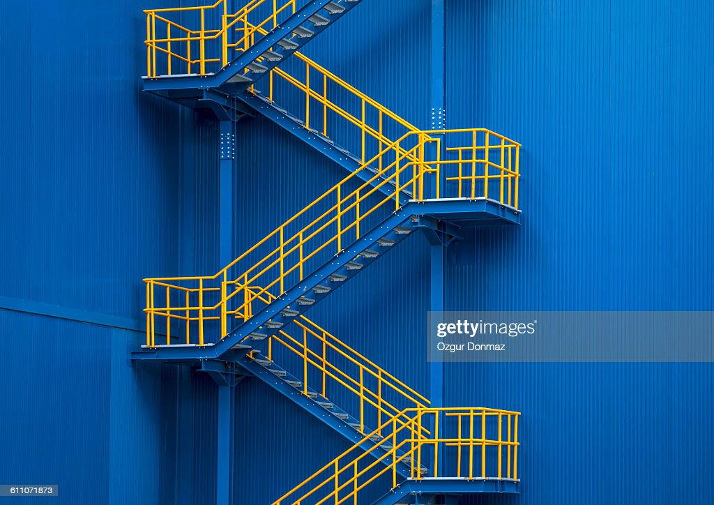Yellow metal staircase against a blue wal : Stock Photo