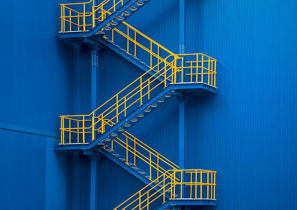 Yellow metal staircase against a blue wal