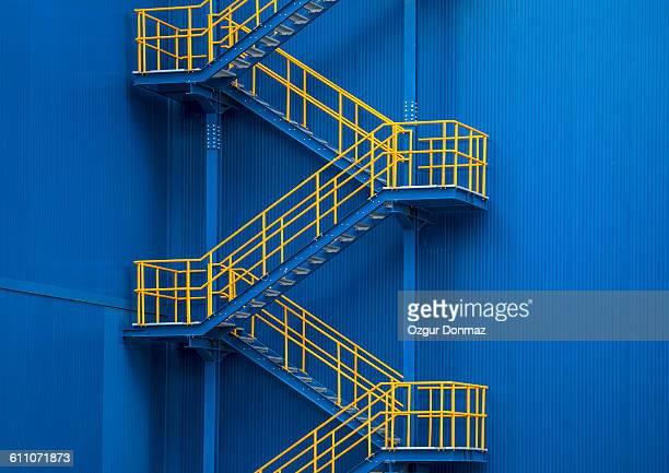 yellow metal staircase against a blue wal - stairs stock photos and pictures