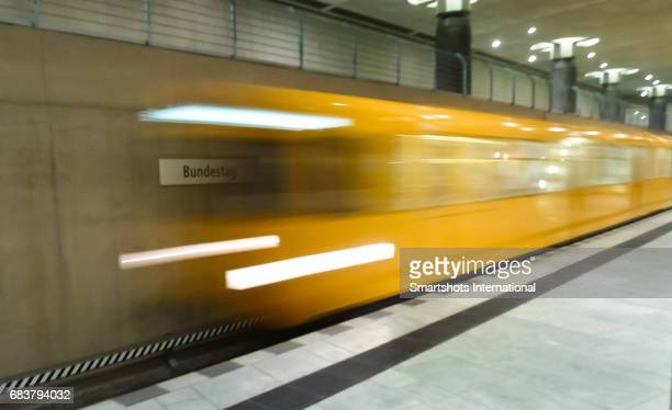 Yellow metro train passing fast past Bundestag metro station in Berlin, Germany
