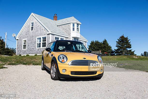 yellow mini cooper parked in front of a seaside cottage - mini cooper stock photos and pictures